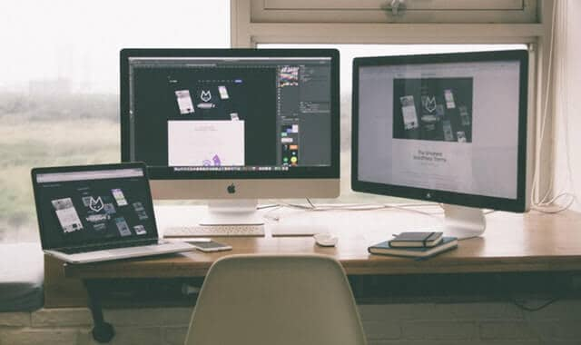 image of three computers on a desk, two imacs and one macbook pro