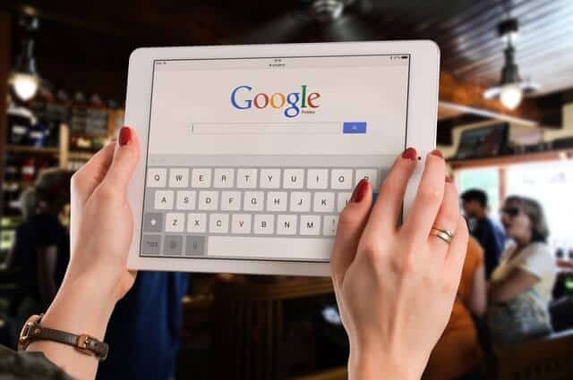 girl holding up an ipda with the google search website displaying